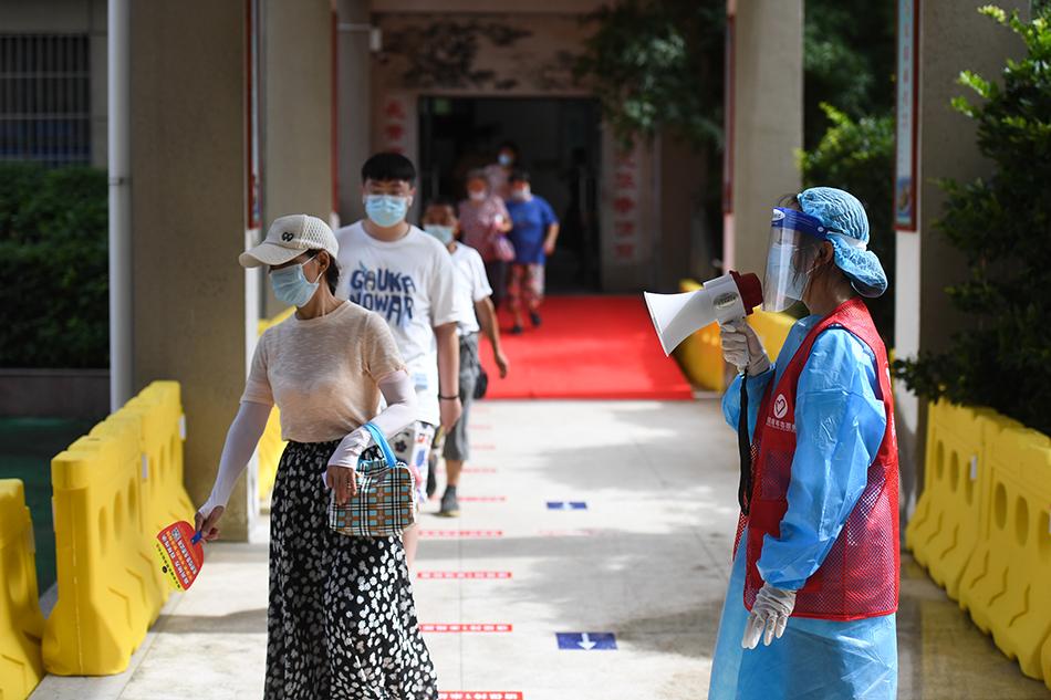 7月29日,在南京市浦口区第二中学核酸检测点,志愿者引导市民有序接受核酸检测取样。 新华社记者 季春鹏 摄
