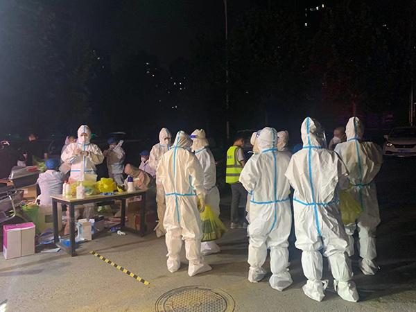 8月2日晚,小区内全套防护服的工作人员。
