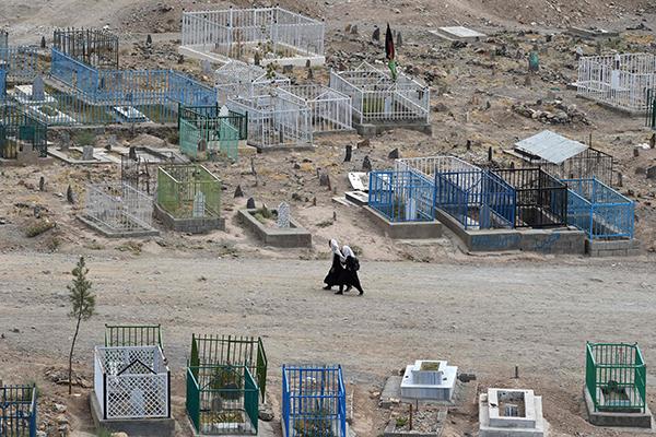当地时间2021年8月14日,阿富汗喀布尔,阿富汗女学生穿过卡萨巴墓地的一条小路。人民视觉 图