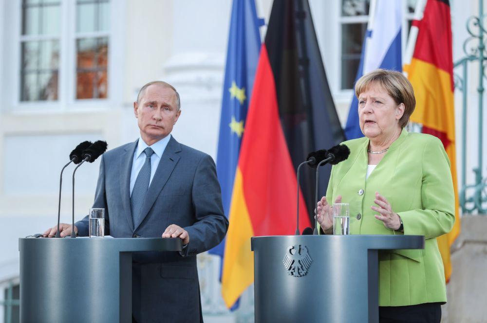 2018年8月18日,在德国首都柏林以北小镇梅泽贝格,德国总理默克尔(右)与来访的俄罗斯总统普京共同出席新闻发布会。(新华社记者单宇琦摄)
