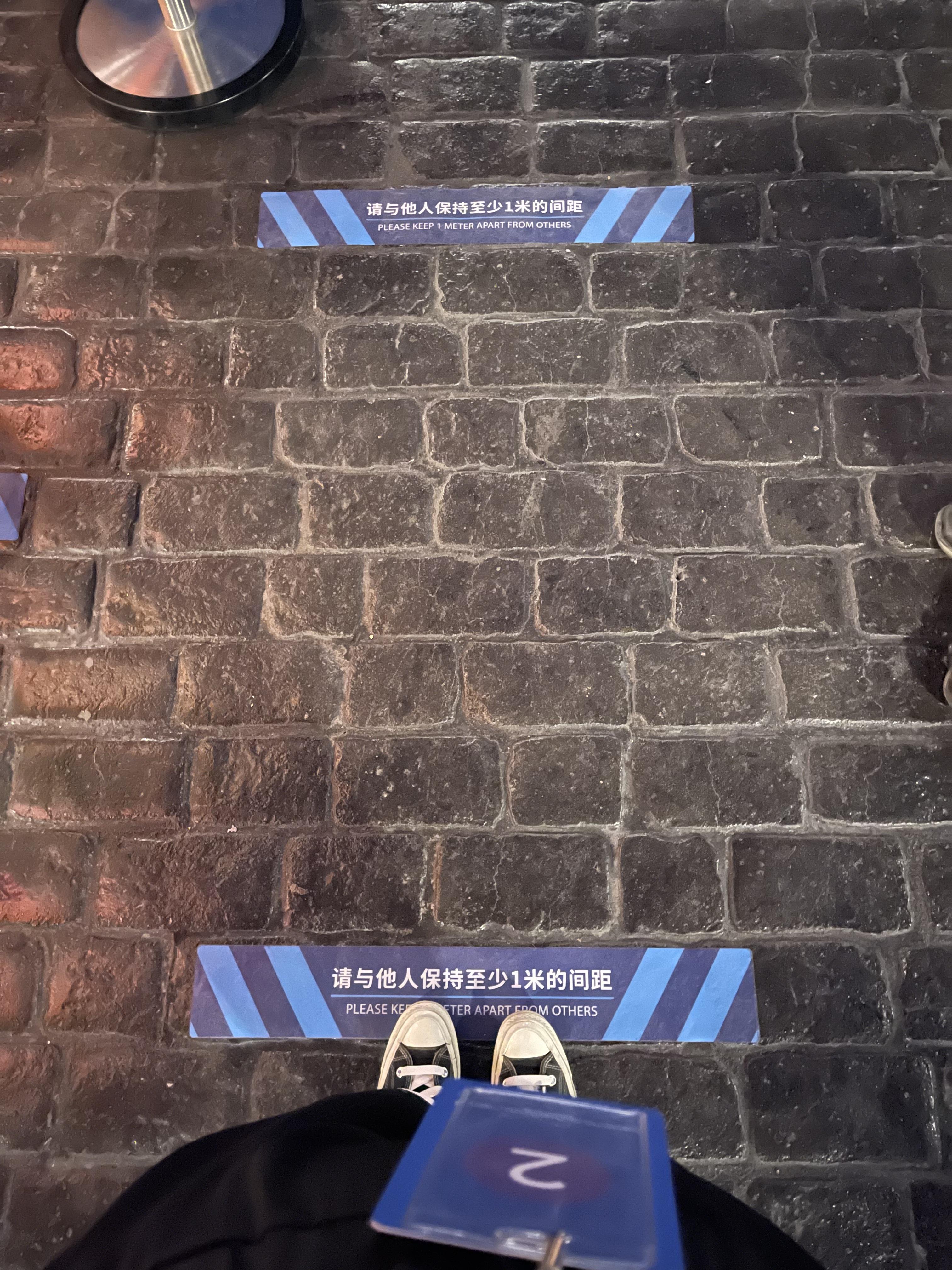 游乐项目的排队通道中,地上每隔一米的位置都贴上了指示贴纸