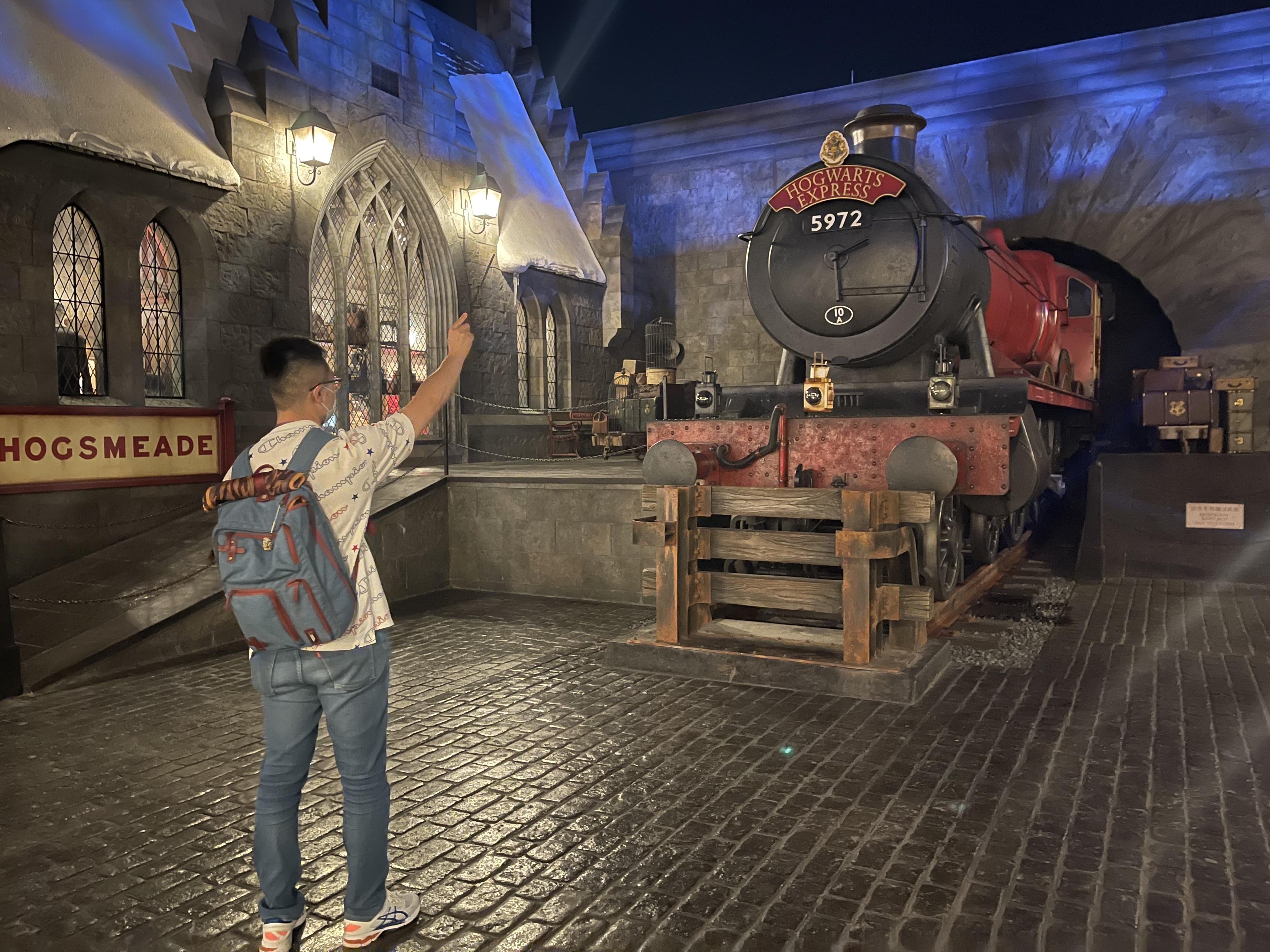 """园区内有不少魔杖可以触发的互动,游客正在尝试用魔杖触发让火车鸣笛的""""魔法""""。"""
