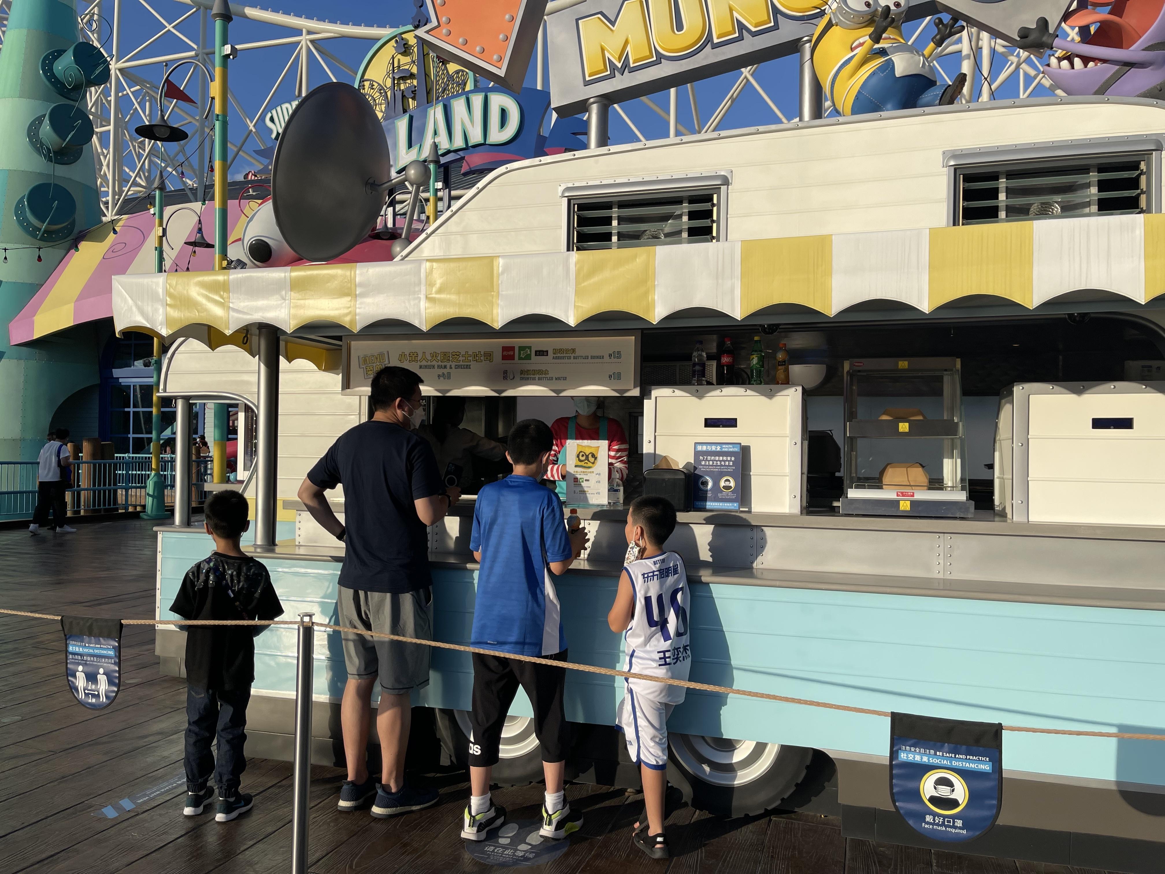 游客在小黄人乐园主题园区中的小吃车前购买食物。