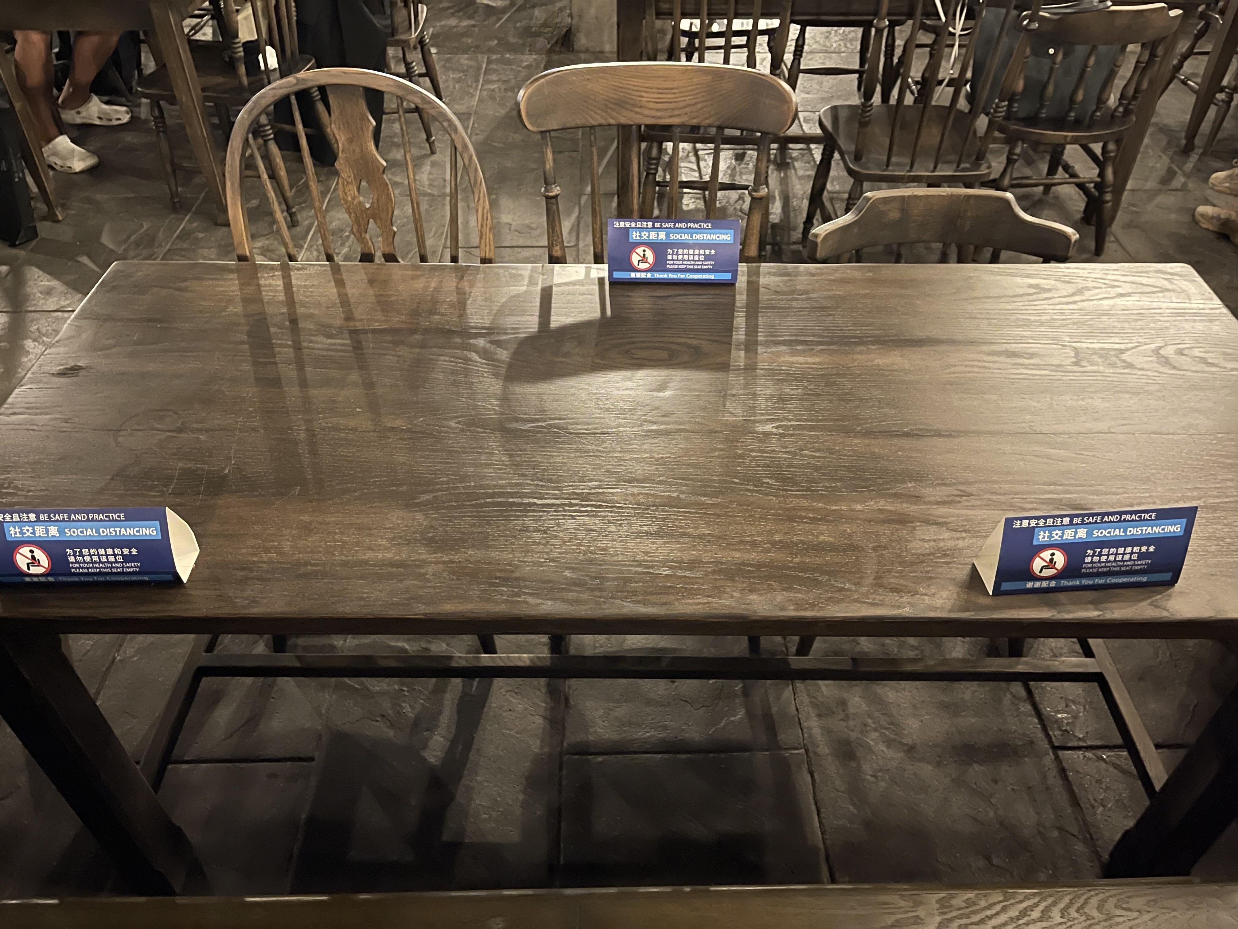 间隔座位的餐桌上牢牢粘上了注意社交距离的指示牌。