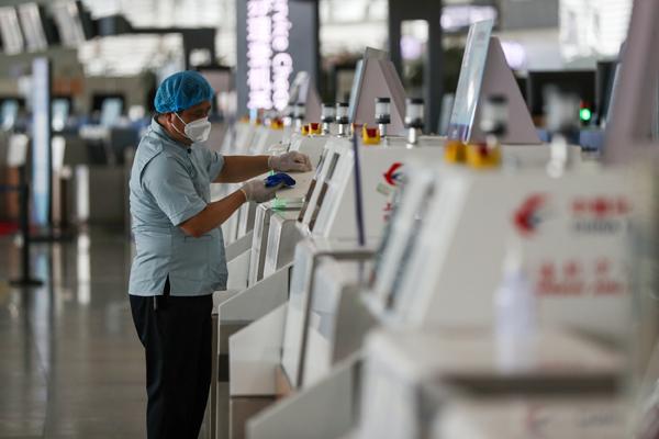 2021年8月26日,江苏南京,南京禄口国际机场T2航站楼,工作人员及时对柜台等人员接触较频繁的部位擦拭消毒。