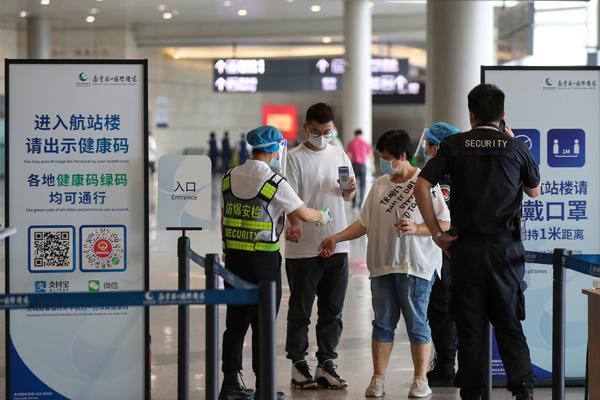 2021年8月26日,江苏南京,禄口国际机场恢复国内航班运行。旅客通过查验健康码、测量体温后方可进入航站楼。