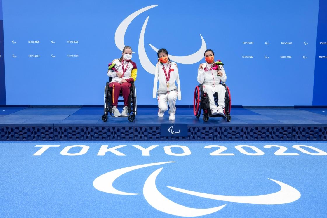 8月27日,盧冬(中)與隊友成姣(右)在頒獎儀式上。當日,在東京殘奧會游泳女子50米蝶泳S5級決賽中,中國選手盧冬奪得冠軍,成姣獲得第三名。新華社 圖
