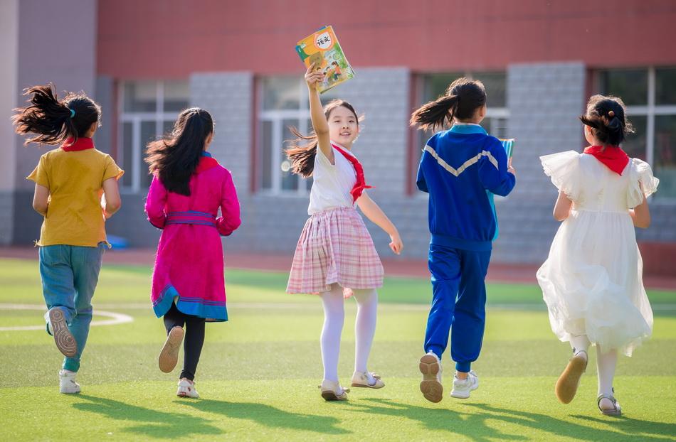 2021年8月30日,在內蒙古自治區呼和浩特市玉泉區民族實驗小學,小學生們手持剛領取的新教材開心地奔跑在校園里。本文圖片 除署名外均為 澎湃影像 人民視覺 圖
