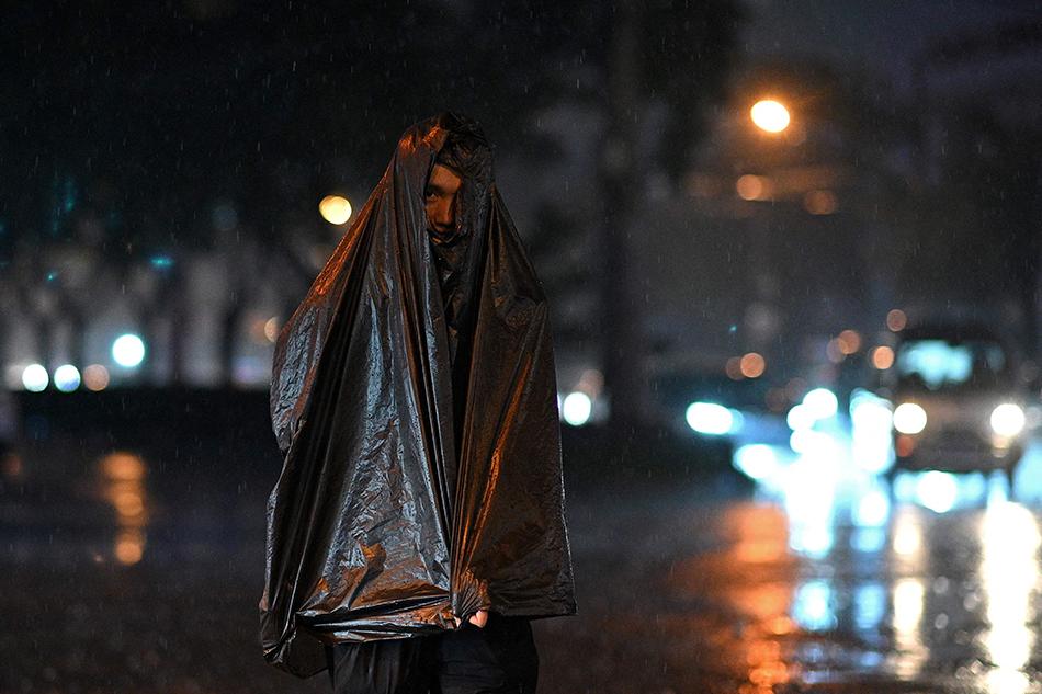 2021年8月23日,北京,雨中的夜晚,市民披著一件黑色塑料袋擋雨。NOEL CELIS /視覺中國 圖