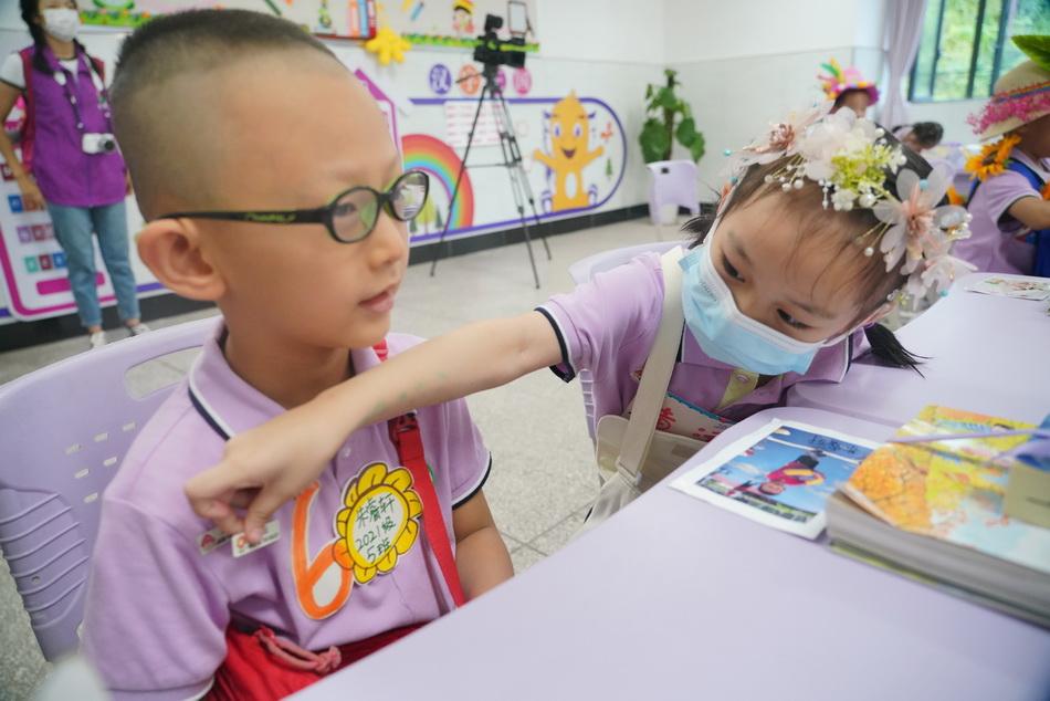 """8月29日,一年級同學們互相認識后,把自己的名字貼在對方的胸前。當日,重慶江北區玉帶山小學北校區的一年級新生們開始報名。為了讓新同學快速融入校園生活,學校開發了""""伙伴""""課程。入學典禮的第一課上,新生們各自找到和自己同月生日的伙伴,通過面對面交流,一同去尋找新班級來增進同學間的融洽度和歸屬感。"""