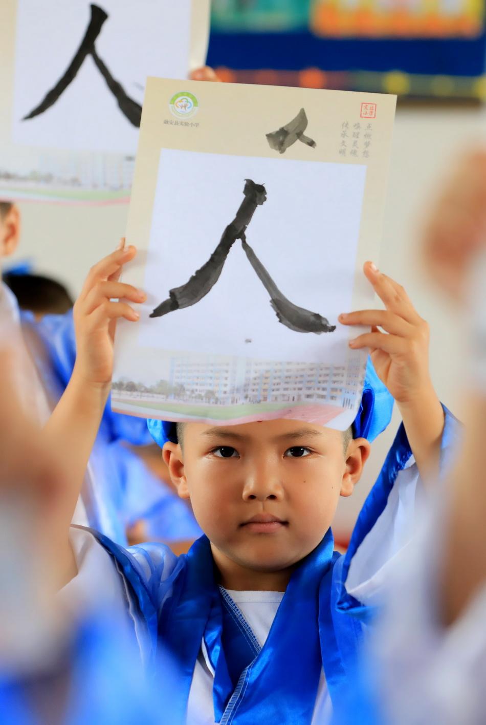 """8月30日,一名小學生展示書寫的""""人""""字。當日,廣西柳州市融安縣實驗小學舉行傳統""""開筆禮"""",一年級新生著漢服,行漢禮,通過""""擊鼓明智、朱砂啟智、啟蒙描紅、放飛夢想""""等中國傳統開學儀式,讓學生體驗中國傳統文化內涵,感受傳統文化魅力。"""