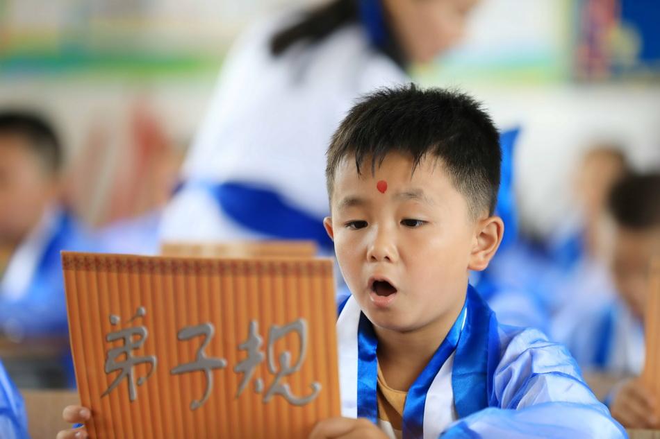 """8月30日,在廣西柳州市融安縣實驗小學""""開筆禮""""儀式上,學生們集體誦讀《弟子規》。"""