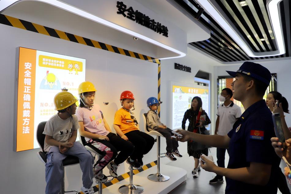 8月27日,湖南常德,學生走進消防科普教育基地學習如何正確佩戴安全帽。