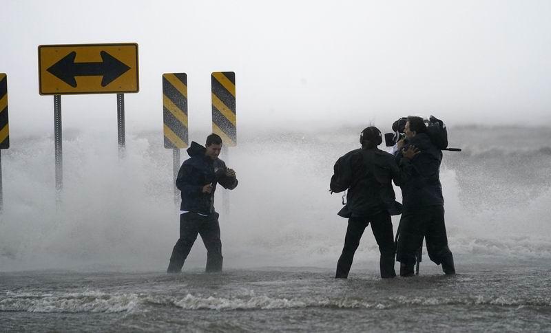 """新聞記者在颶風""""艾達""""逼近前的龐恰特雷恩湖畔進行現場報道。"""