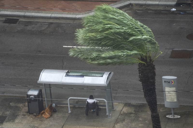 """""""艾達""""登陸帶來狂風暴雨,一名男子在公交車站避難。"""
