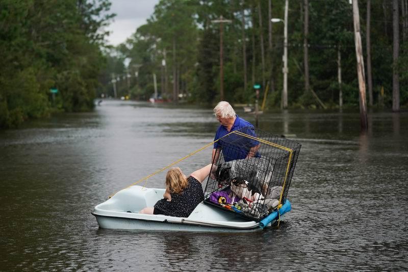 2021年8月30日,在密西西比州,一對夫婦用劃艇運送他們的狗穿過被洪水淹沒的社區。