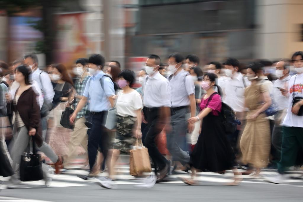當地時間2021年8月23日,日本東京,通勤者戴著口罩在街頭行走。