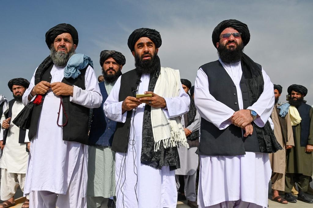"""當地時間2021年8月31日,阿富汗喀布爾,在最后一批美軍撤離阿富汗數小時后,塔利班發言人穆賈希德(中)在喀布爾機場稱,""""祝賀阿富汗……這場勝利屬于我們所有人。"""