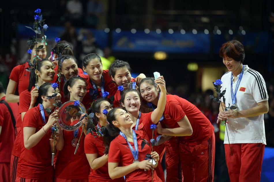 2014年10月12日,意大利米蘭,女排世錦賽決賽后,郎平在一旁微笑著看女排隊員們自拍慶祝獲得亞軍。