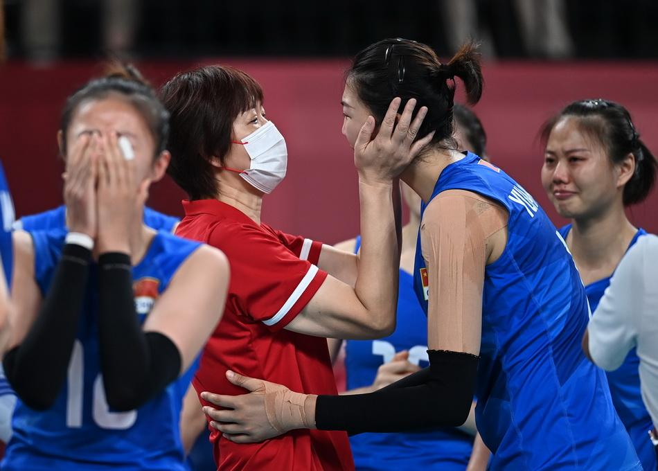 2021年8月2日,中國女排結束最后一場小組賽對決,面對小組實力最弱的阿根廷隊,中國女排以連下三局,最終以2勝3負戰績排名小組第五,無緣晉級淘汰賽。比賽后,郎平(左二)與球員安慰隊員袁心玥(右二)。