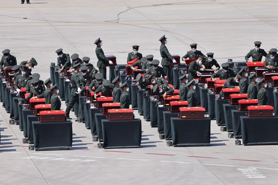 2021年9月2日,沈陽桃仙國際機場,在棺槨整理區,禮兵戰士認真擦拭每一個棺槨,并覆蓋上五星紅旗。