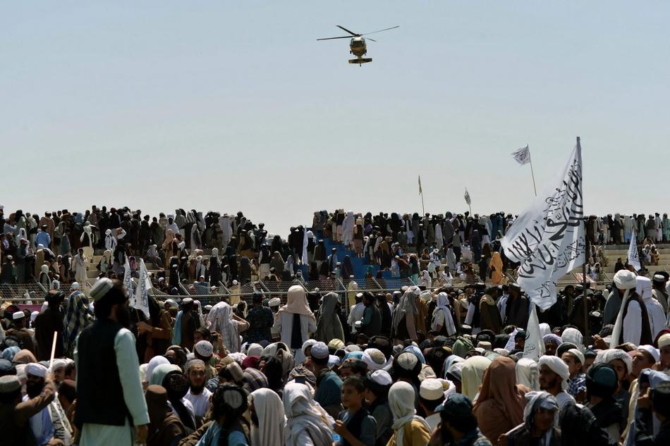 當地時間2021年9月1日,塔利班支持者聚集在坎大哈,一架直升機從上空飛過。