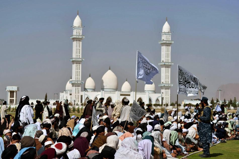 當地時間2021年9月1日,塔利班支持者盤腿坐在草坪上。