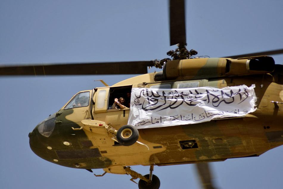 當地時間2021年9月1日,一架懸掛著白色塔利班旗幟的黑鷹直升機出現在慶典現場。