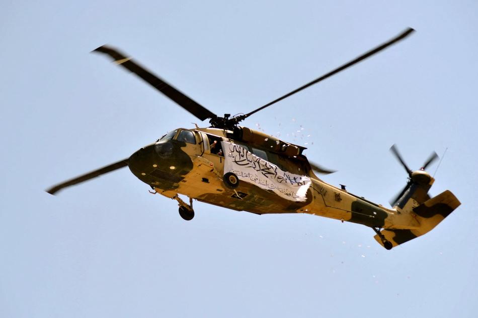 當地時間2021年9月1日,一架懸掛著塔利班旗幟黑鷹直升機飛過坎大哈上空。