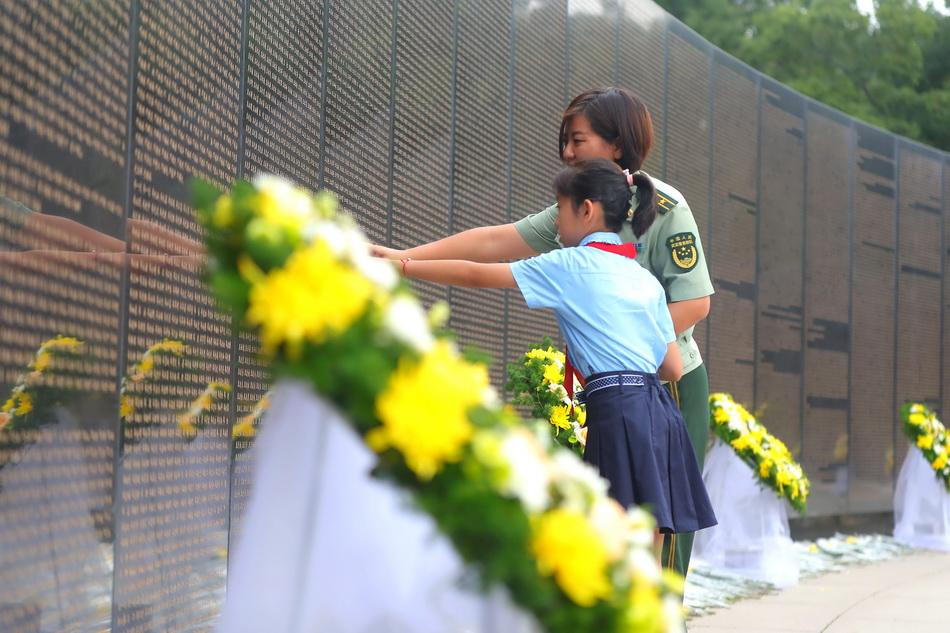 2021年9月3日,武警戰士和小學生在志愿軍烈士英名墻前緬懷英烈。