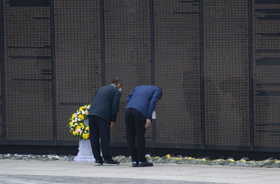 人們向烈士獻花致敬,并瞻仰烈士英名墻。
