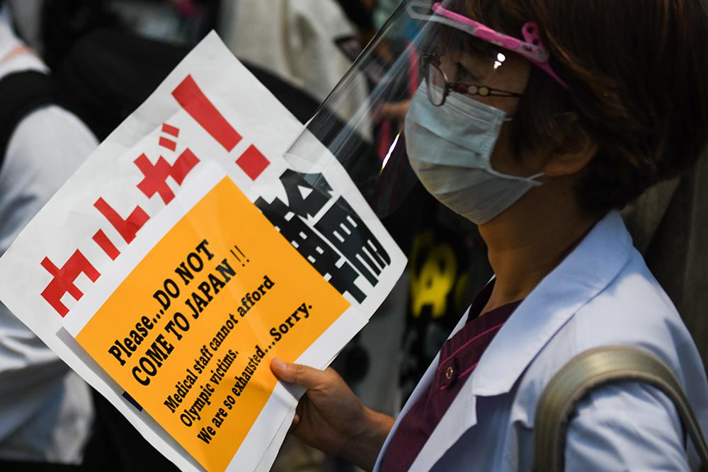 当地时间2021年6月23日,日本东京,在距离2020东京奥运会开幕倒计时一个月之际,东京民众走上街头,举行反奥运示威游行。人民视觉 图
