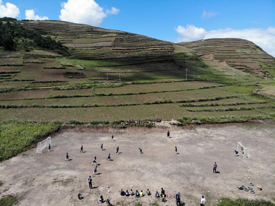 2021年9月2日,大山中,白云下,孩子們在球場上踢球。目前,瓦吾小學還沒有專業完備的足球場,孩子們晴天在沙塵里奔跑,雨天在泥濘中前行。