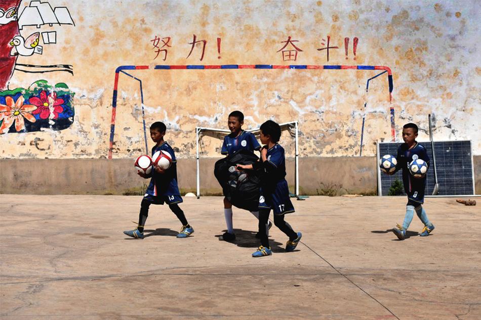 2021年9月2日,孩子們捧著足球準備去上訓練。瓦屋小學的圍墻上也畫有球門,每到課間,孩子們會對著墻練習射門,久而久之,上面留下了許多球印。