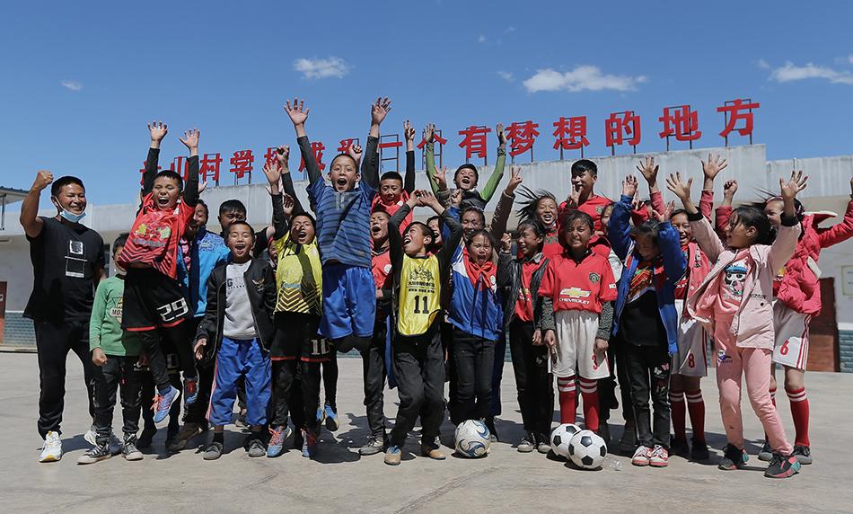 """2020年5月8日,足球隊員和曲比史古老師(左一)在學校合影。他們身后,瓦吾小學的屋頂上寫著""""讓山村小學成為一個有夢想的地方""""。"""