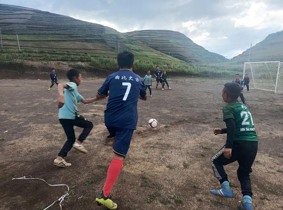 曲比史古和孩子們一起在足球場上練習。