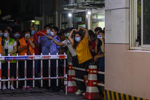 2021年9月3日,上海市祝和苑北區,居民在小區內對著前來迎接的親友做比心的動作。