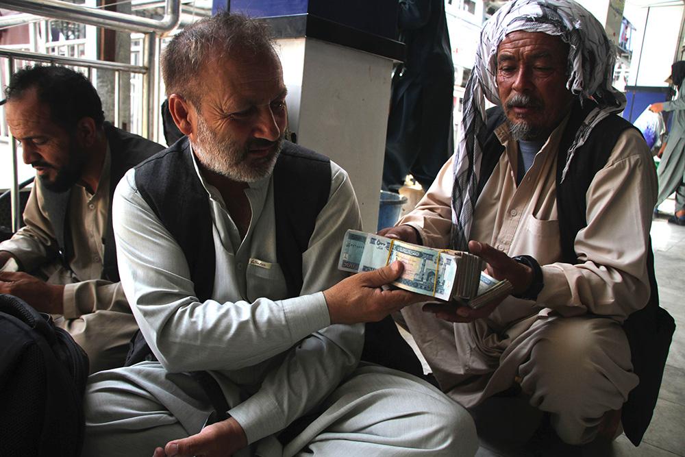 當地時間2021年9月4日,阿富汗人在喀布爾一家貨幣交易市場內兌換貨幣。