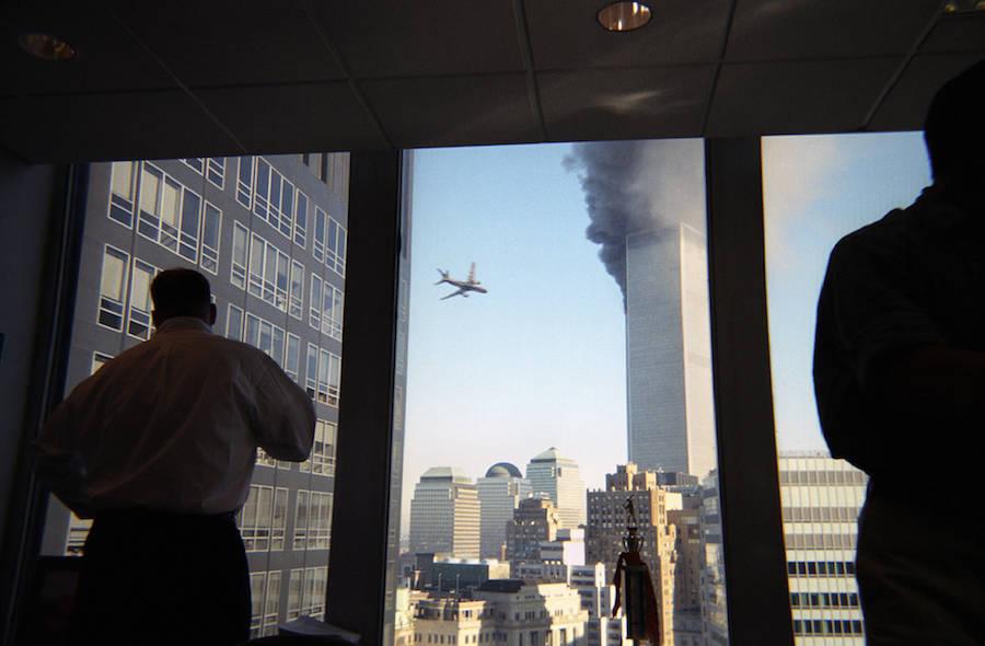 2001年9月11日,美國紐約,濃煙從世貿中心北塔滾滾而出,15分鐘后第二架聯合航空公司175號航班撞擊世貿中心南塔。從附近的辦公樓可以看到,該航班正以最快的速度飛往世界貿易中心。