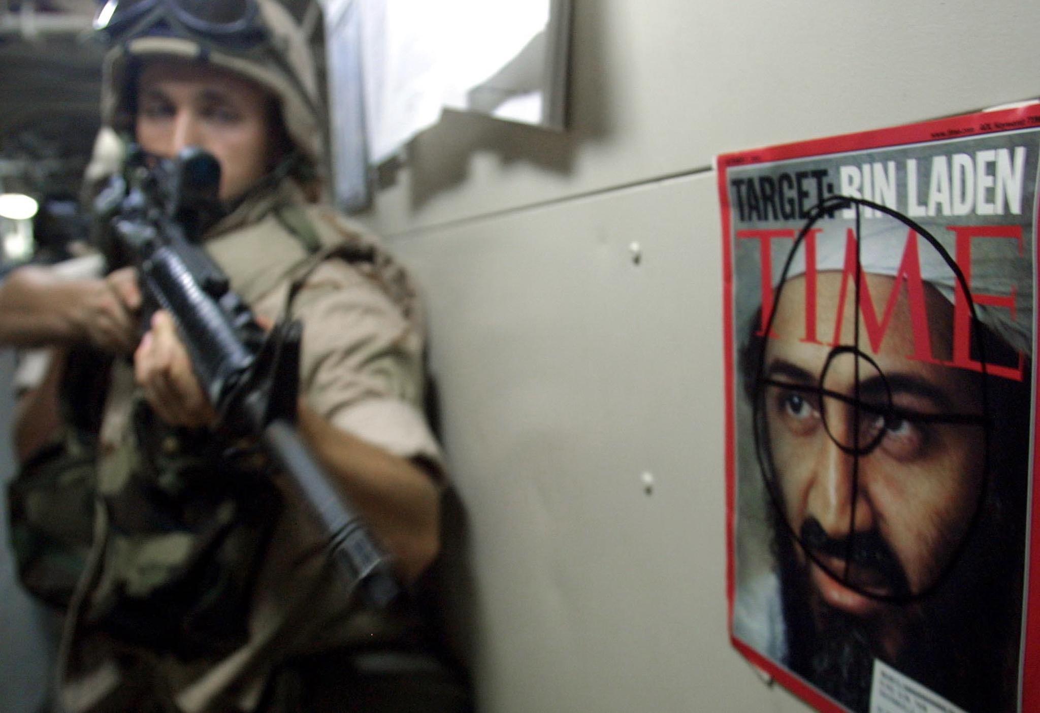 """当地时间2001年12月12日,美国海军""""惠特比岛""""号两栖攻击舰上,一名海军陆战队队员从墙上贴着的本·拉登时代杂志封面前经过。"""