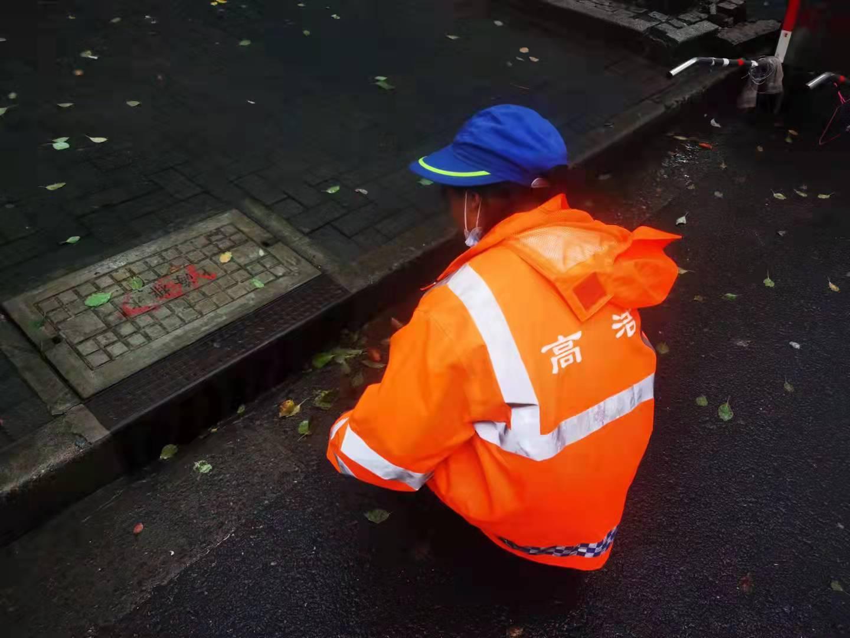 环卫工人清理道路排水口周边落叶、垃圾和淤泥。