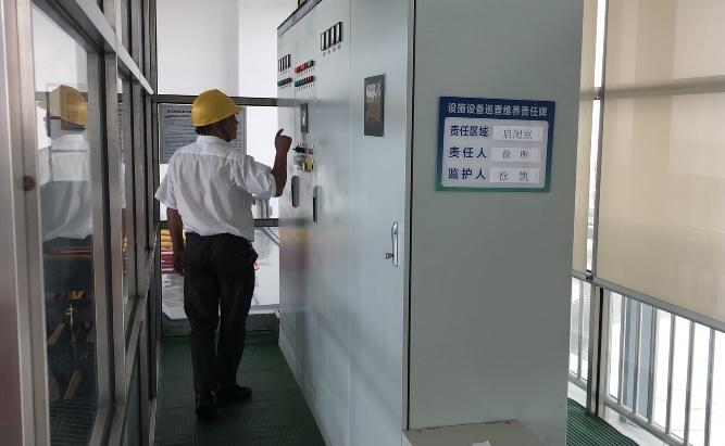 工作人员在配电室检查水闸设备