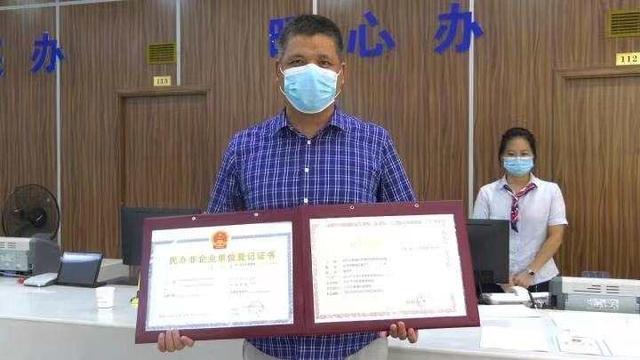9月14日,金华市婺城区英华时代教育培训有限公司负责人倪俞华从工作人员手中接过两本全新的证件。 钱江晚报 图