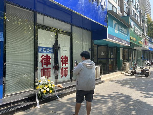 命案发生次日,有武汉市民订鲜花让外卖小哥送到案发现场,祭奠遇害的薛伟幸律师。 本文图均为澎湃新闻记者 谢寅宗 图