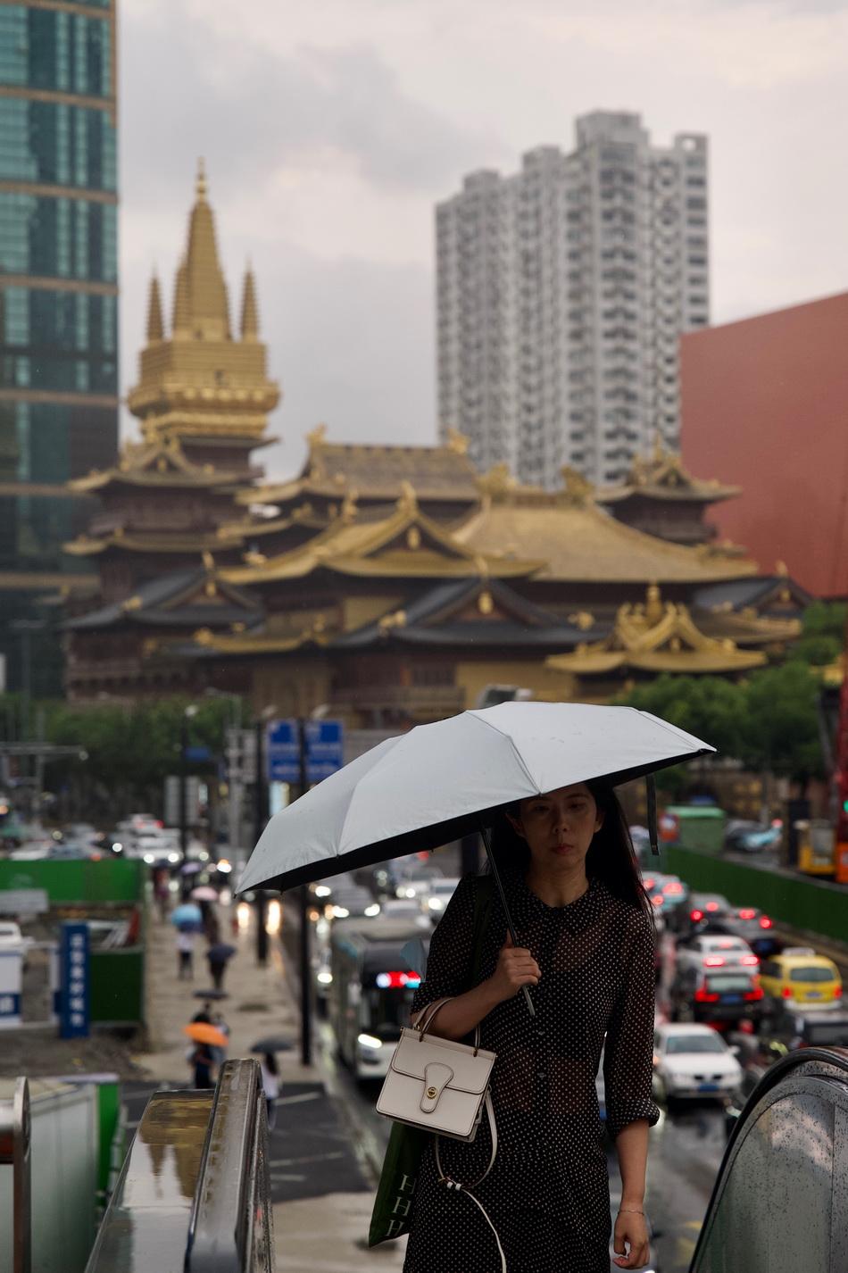 2021年9月10日,上海延安中路华山路,行人撑伞步入天桥搭乘公共交通,雨天让地面交通变得拥堵。