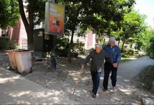 黄刘氏在儿子黄才荣的搀扶下在小区散步。 新华社 资料图