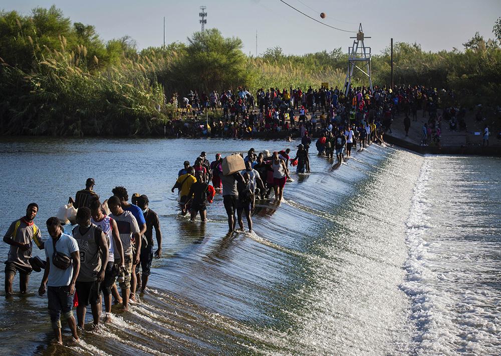 当地时间2021年9月17日,大批海地移民通过一座大坝从墨西哥进入美国。得州一名众议员18日前往该营地后表示,桥下的移民人数已接近1.5万人。