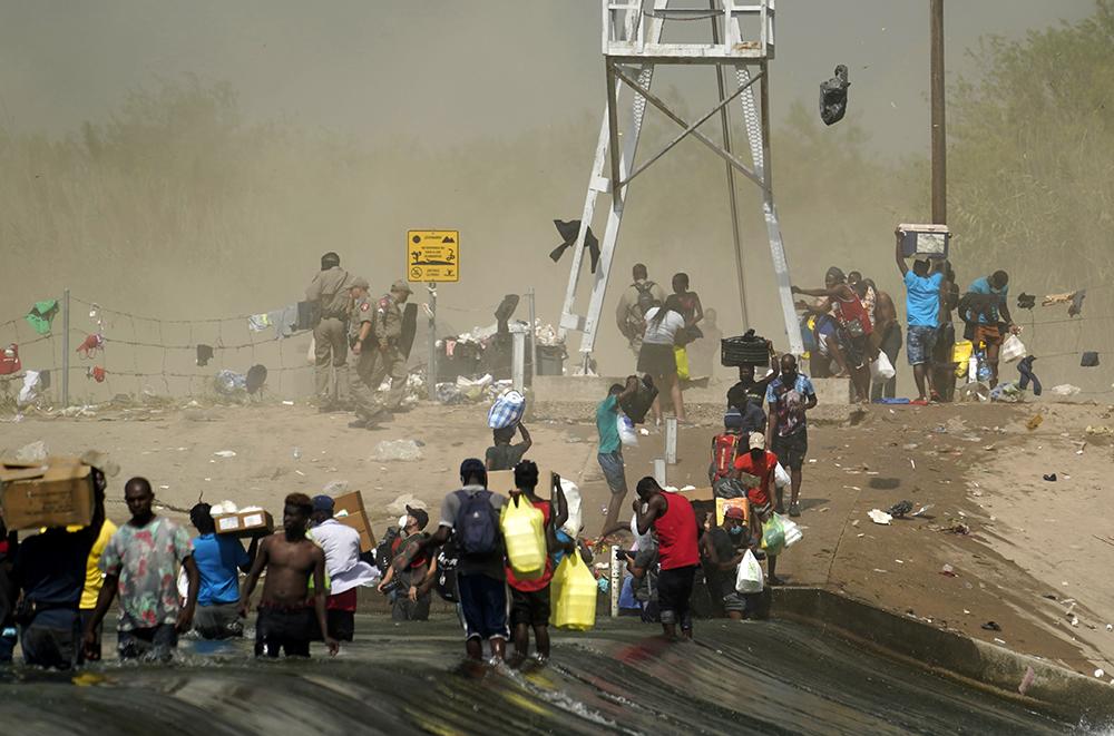 当地时间2021年9月18日,美国德克萨斯州,海地移民通过大坝抵达美国。