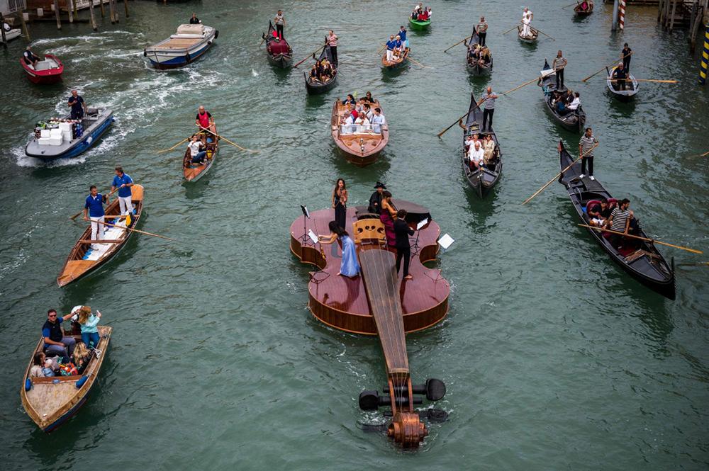 当地时间2021年9月18日,音乐家在意大利威尼斯河道上一条形状为小提琴的船上演奏音乐。