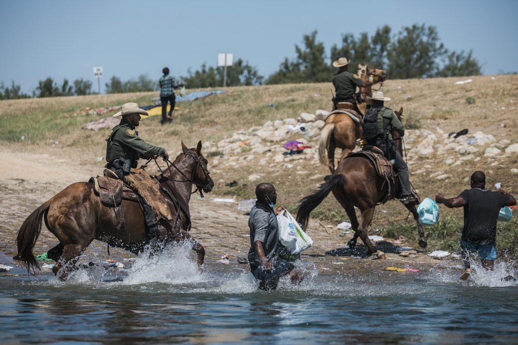 当地时间2021年9月19日,美国得克萨斯州边境城市德尔里奥,里奥格兰德河边,美国海关和边境保护局骑警试图控制非法移民,因为他们试图从阿库纳城穿越格兰德河进入得克萨斯。